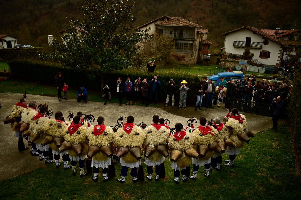 . A group of Joaldunaks called Zanpantzar, pose for onlookers before they take part in the Carnival between the Pyrenees villages of Ituren and Zubieta, northern Spain, Monday, Jan. 30, 2017. In one of the most ancient carnivals in Europe, dating from before the Roman empire, companies of Joaldunak (cowbells) made up of residents of two towns, Ituren and Zubieta, parade the streets costumed in sandals, lace petticoats, sheepskins around the waist and shoulders, coloured neckerchiefs, conical caps with ribbons and a hyssop of horsehair in their right hands and cowbells hung across their lower back. (AP Photo/Alvaro Barrientos)