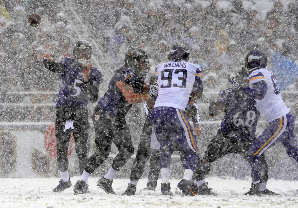 . Baltimore Ravens quarterback Joe Flacco (5) throws to a receiver as snow falls in the first half of an NFL football game against the Minnesota Vikings, Sunday, Dec. 8, 2013, in Baltimore. (AP Photo/Gail Burton)