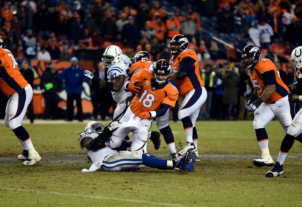 . Peyton Manning (18) of the Denver Broncos gets sacked late in the fourth quarter by Erik Walden (93) of the Indianapolis Colts.  The Denver Broncos played the Indianapolis Colts in an AFC divisional playoff game at Sports Authority Field at Mile High in Denver on January 11, 2015. (Photo by Tim Rasmussen/The Denver Post)