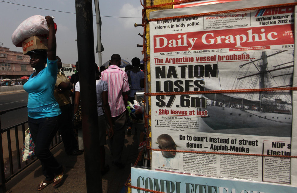 Description of . People walk past a vendor selling newspapers with its front page reporting about an Argentine naval vessel involved in a debt dispute, in Acrra December 20, 2012. The Argentine naval vessel detained in Ghana at the request of a hedge fund seeking payment on defaulted government bonds left the West African country on Wednesday, a port official said. The ARA Libertad, a tall sailing ship used for training, was detained on a court order obtained by NML Capital Ltd, which claims it is owed $300 million resulting Argentina's debt default in 2002. REUTERS/Luc Gnago