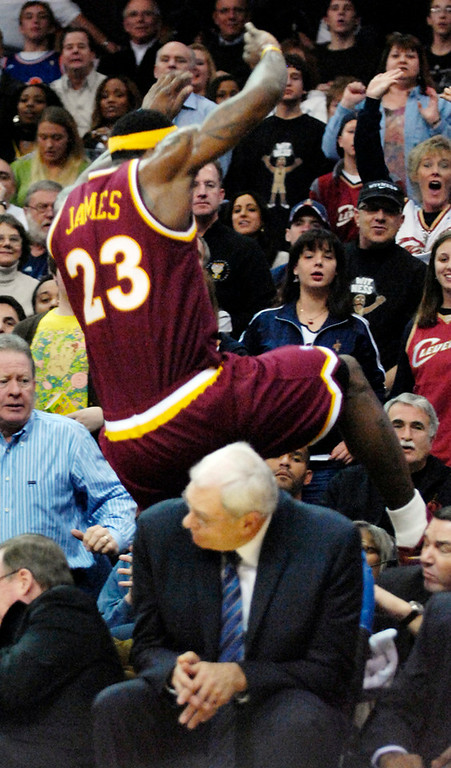 . Jeff Forman/JForman@News-Herald.com LeBron James chases a loose ball and jumps over Phil Jackson in the fourth quarter Thursday at Quicken Loans Arena.