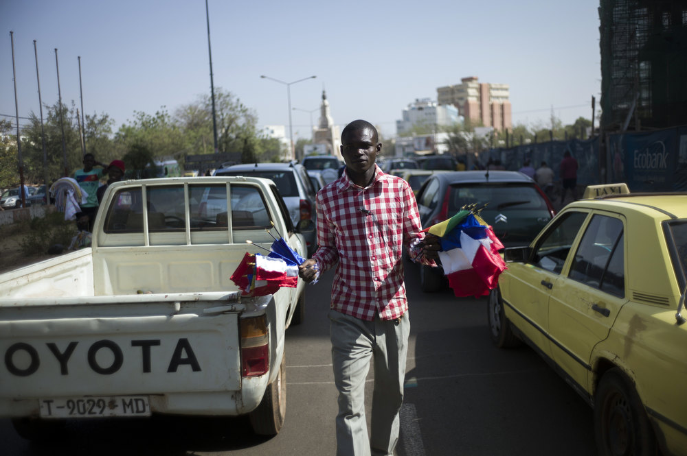 Description of . A Malian man sells flags, including French ones, on a street of Bamako on January 17, 2013. France now has 1,400 troops on the ground in Mali, more than half the total of 2,500 it plans to deploy in its former colony, Defence Minister Jean-Yves Le Drian said on Thursday. FRED DUFOUR/AFP/Getty Images