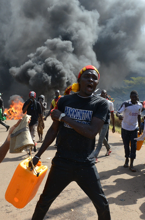 . Protesters walk outside the parliament in Ouagadougou on October 30, 2014 as cars and documents burn outside. Hundreds of angry demonstrators in Burkina Faso stormed parliament on October 30 before setting it on fire in protest at plans to change the constitution to allow President Blaise Compaore to extend his 27-year rule. ISSOUF SANOGO/AFP/Getty Images