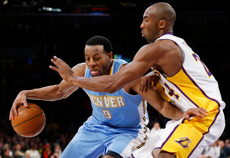 . Denver Nuggets\' Andre Iguodala (L) dribbles as Los Angeles Lakers\' Kobe Bryant (R) defends during the first half of their NBA basketball game in Los Angeles January 6, 2013. REUTERS/Danny Moloshok