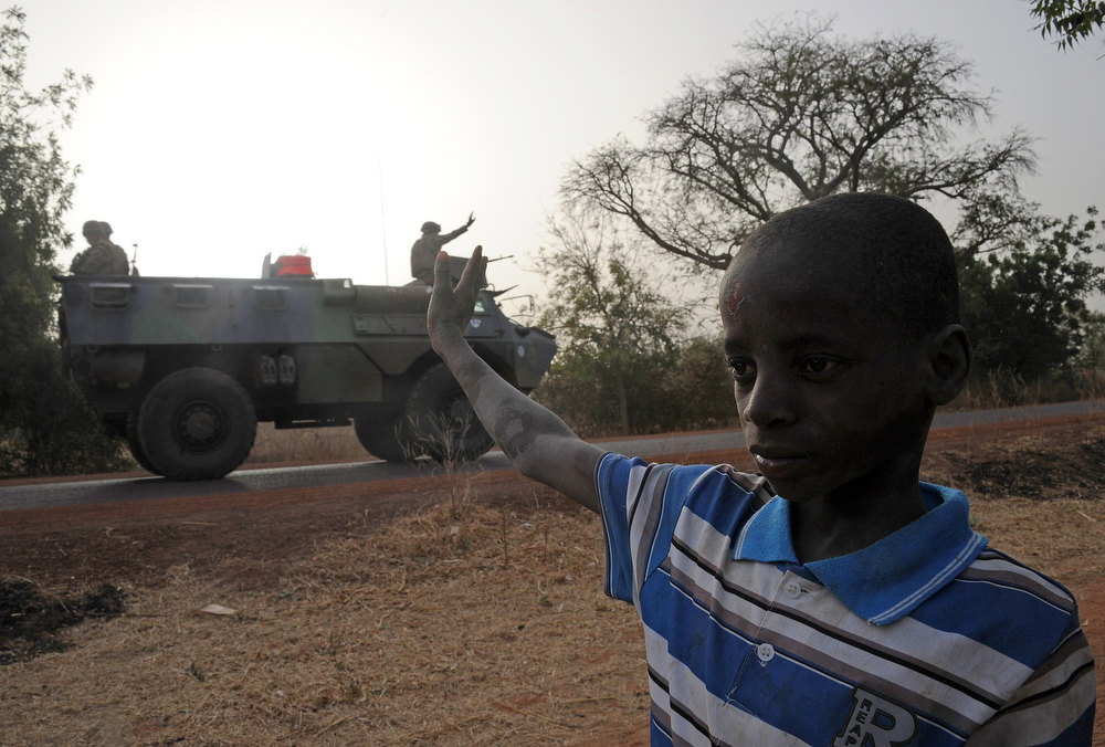 Description of . A man waves at a convoy of French army vehicules as French soldiers arrive in Sevare, in the Mopti region of Mali, on February 1, 2013. President Francois Hollande prepared to visit Mali as French-led troops worked today to secure the last Islamist stronghold in the north after a lightning offensive against the extremists. Hollande, whose surprise decision to intervene in Mali three weeks ago has won broad support at home, will travel to the fabled city of Timbuktu and hold a working lunch in the capital with Mali\'s interim president Dioncounda Traore, the Malian presidency said. PASCAL GUYOT/AFP/Getty Images