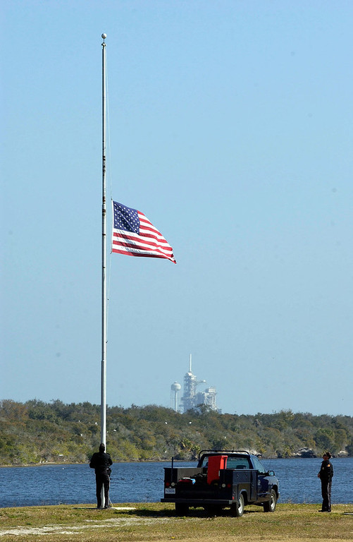 . NASA security officers Bruce Forton and Mike Orr lower the U.S.  flag and remove the flag for Space Shuttle Columbia  February 1, 2003 at Kennedy Space Center in Florida. In the background is launch pad 39-A which Columbia used to lift into orbit. The shuttle broke into pieces and went down over Texas as it attempted to land. (Photo by Matt Stroshane / Getty Images)