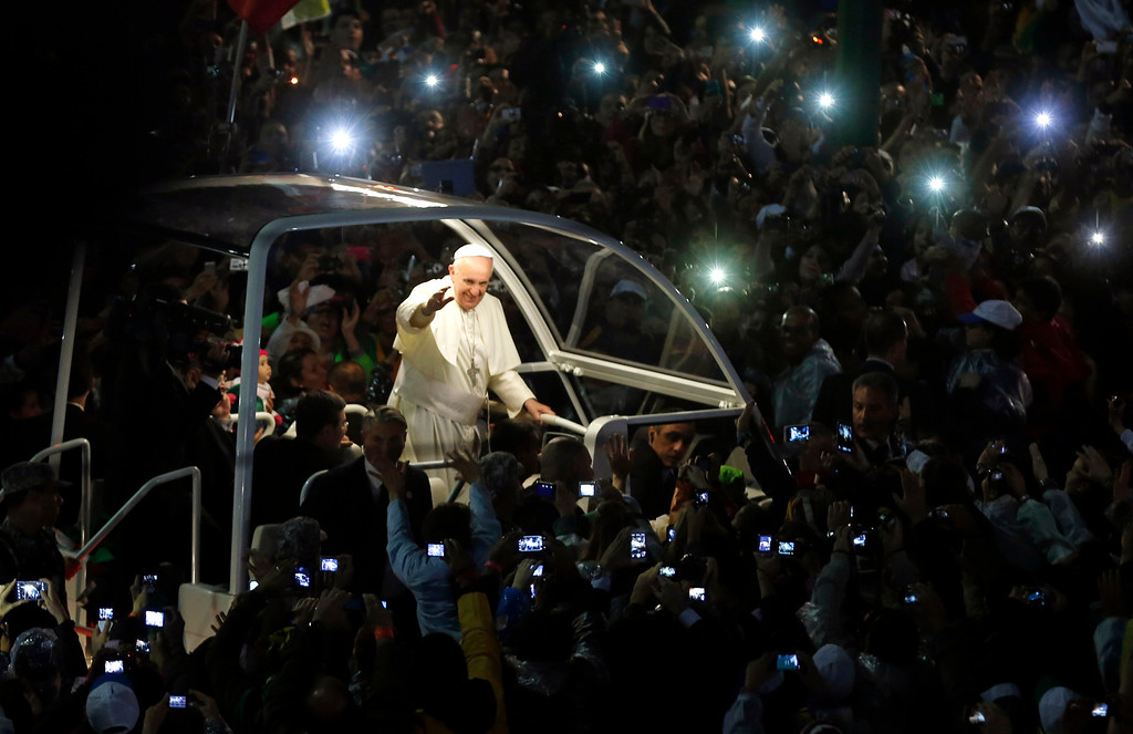 . Pope Francis arrives for a World Youth Day celebration at the Copacabana beachfront in Rio de Janeiro, Brazil, Thursday July 25, 2013. Cheering pilgrims from 175 nations lined the beachfront drive to catch a glimpse of Francis. The popemobile stopped several times for Francis to kiss babies - and take a sip of his beloved mate, the traditional Argentine tea served in a gourd with a straw, that was handed up to him by someone in the crowd. (AP Photo/Enric Marti)