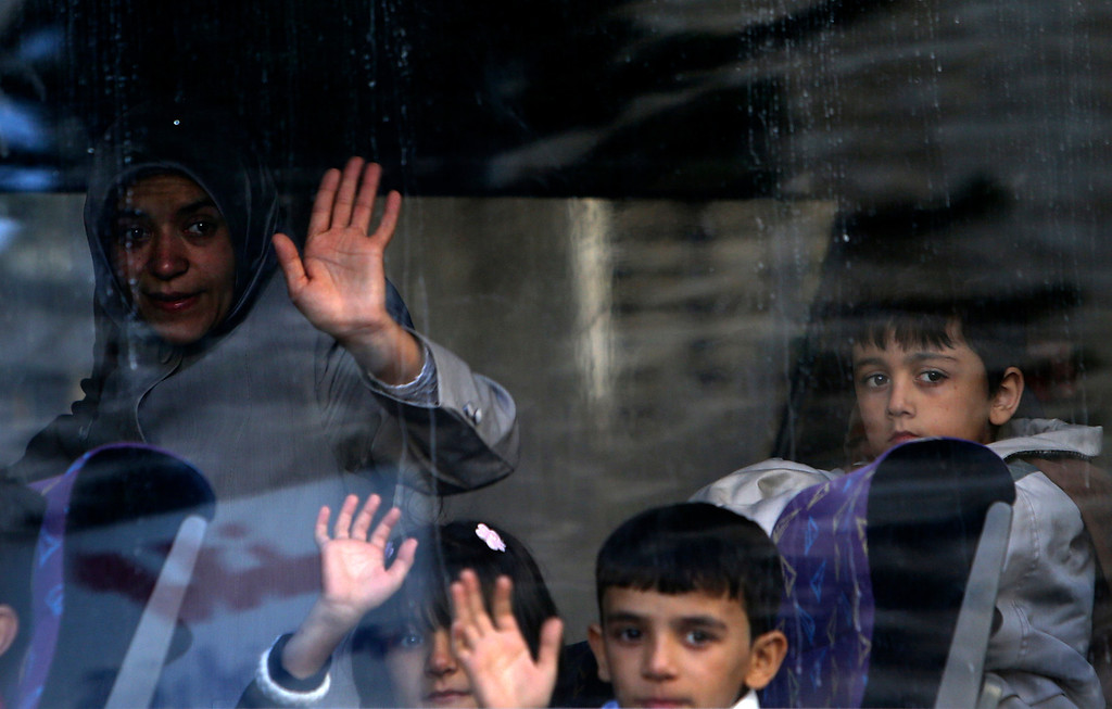. A Syrian refugee family waves to relatives after boarding a bus to Beirut International Airport for a flight to Germany where they have been accepted for temporary resettlement, at the International Organization for Migration office in Beirut, Lebanon, Thursday, Oct. 10, 2013. The dozens of Syrians heading to Germany on Thursday were the second  batch of the 4,000 refugees that Germany has accepted to receive on two-year visas while Syria remains mired in a two-year civil war that has killed over 100,000 people, displaced 5 million within their own country, and prompted another 2 million people to flee the country as refugees. (AP Photo/Hussein Malla)