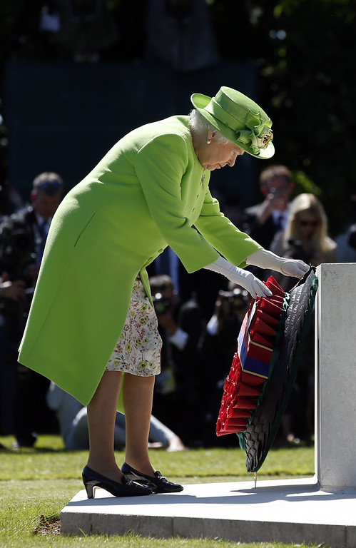. Queen Elizabeth II lays a wreath at the foot of the Cross of Sacrifice in the centre of Commonwealth War Graves Commission Cemetery during a service of remembrance on June 6, 2014 in Bayeux, France.  (Photo by Jonathan Brady - Pool/Getty Images)