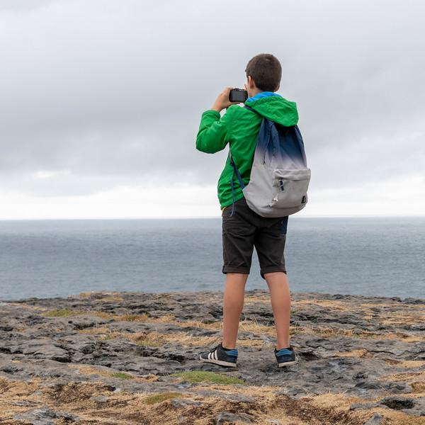 Tourist photographing at prehistoric Fort of Dun Aonghasa, Kilronan, Inishmore, Aran Islands, County Galway, Republic of Ireland