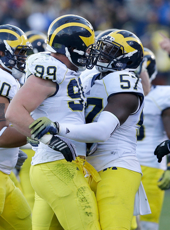 . Michigan defensive tackle Matthew Godin (99), left, celebrates with defensive end Frank Clark (57) after Godin intercepted the ball during the first half of an NCAA college football game against Northwestern in Evanston, Ill., Saturday, Nov. 8, 2014. Michigan won 10-9. (AP Photo/Nam Y. Huh)