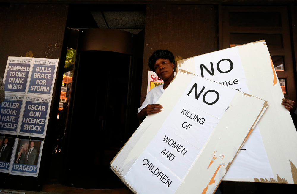 Description of . A woman holds up signs as she and others protest outside the Pretoria Magistrates court during the bail application of