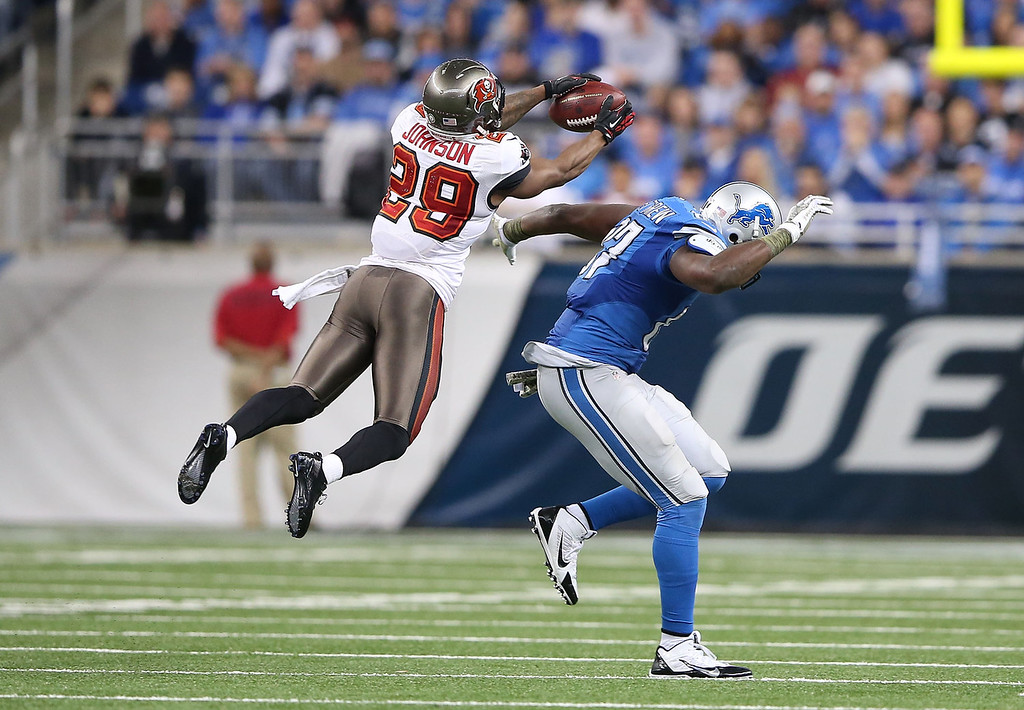 . Leonard Johnson #29 of the Tampa Bay Buccaneers intercepts a pass in front of Brandon Pettigrew #87 of the Detroit Lions and runs it back 48 yards for a touchdown during the second quarter of the game at Ford Field on November 24, 2013 in Detroit, Michigan.  (Photo by Leon Halip/Getty Images)