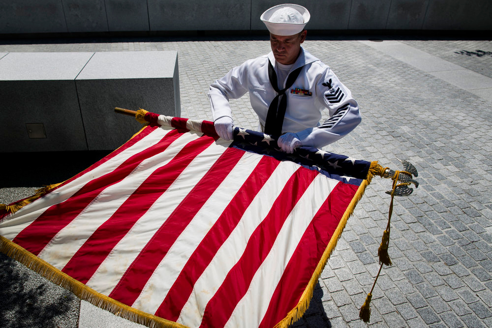 . Navy Petty Officer Mark Jones of the Navy Operational Support Center of New York City rolls the American flag after a Memorial Day wreath laying at the Franklin D. Roosevelt Four Freedoms Park on Roosevelt Island, Monday, May 27, 2013, in New York. (AP Photo/John Minchillo)