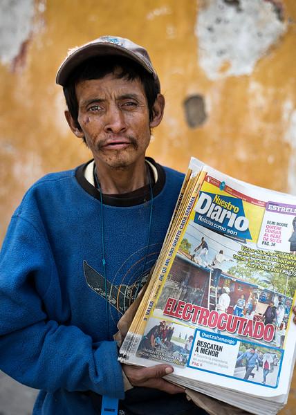 Guatemalan newspaper vendor.