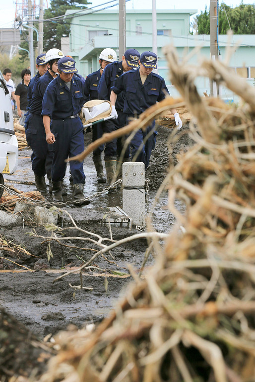 . Rescue workers carry the body of a landslide victim after a powerful typhoon hit Izu Oshima island, about 120 kilometers (75 miles) south of Tokyo, Wednesday morning, Oct. 16, 2013. Typhoon Wipha triggered landslides and caused multiple deaths on the Japanese island, before sweeping up the country\'s east coast, grounding hundreds of flights and paralyzing public transportation in Tokyo during Wednesday morning\'s rush hour. (AP Photo/Kyodo News)