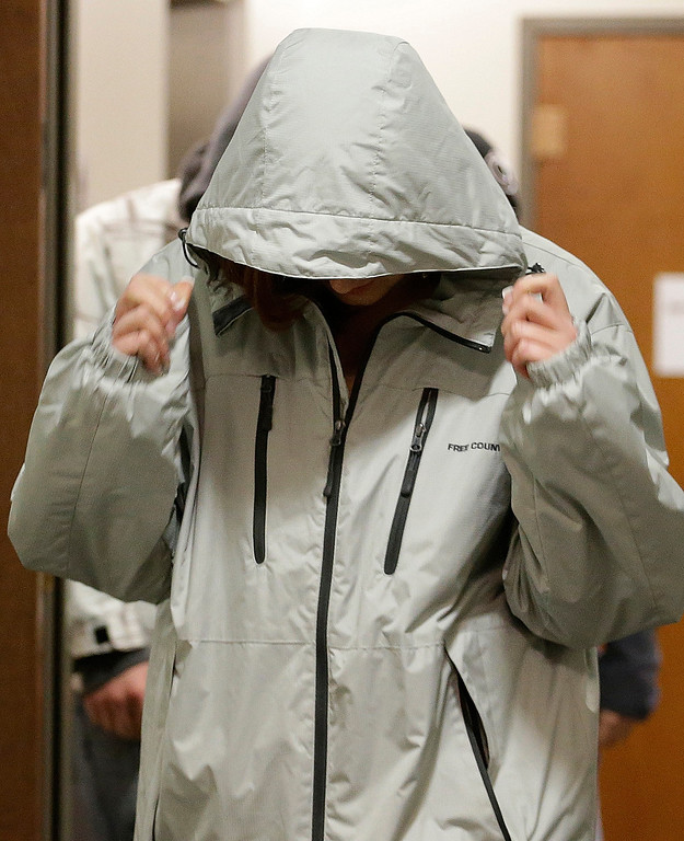. A woman covers her head as she arrives at district court for the arraignment of Aurora theater shooting suspect James Holmes in Centennial, Colo., on Tuesday, March 12, 2013. (AP Photo/Ed Andrieski)