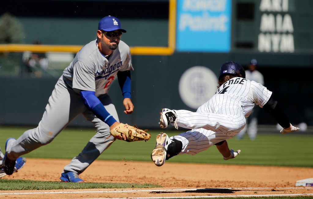 . Colorado Rockies\' Josh Rutledge (14) dives to first base to beat the tag by Los Angeles Dodgers first baseman Adrian Gonzalez (23) Wednesday, Sept. 17, 2014, in Denver. (AP Photo/Jack Dempsey)