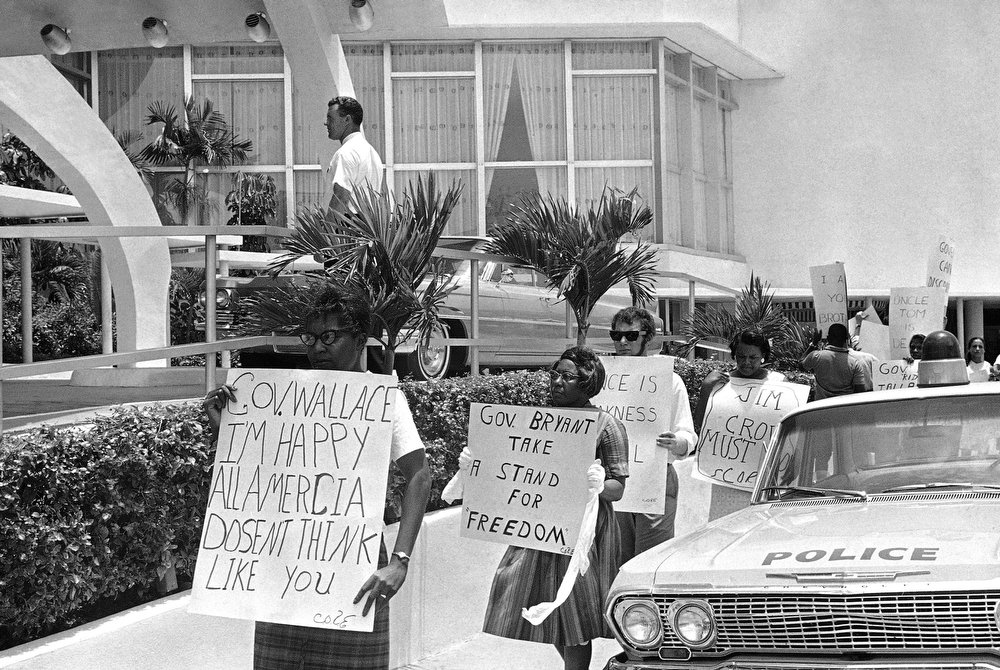 . Representatives of the Congress of Racial Equality (CORE) carry signs on a picket line where the 55th annual Governors Conference opens in Miami Beach, Florida, July 21, 1963. During the picketing asking for racial equality, Governor George Wallace of Alabama was inside holding a news conference. (AP Photo)