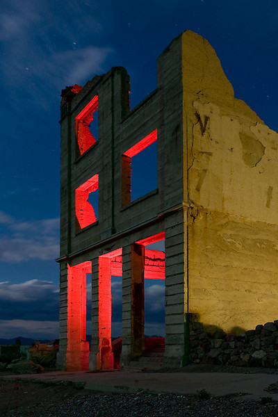 Financial Meltdown  Cook Bank Building in Rhyolite, NV.  Ambient moon light, combined with sidelighting from a Coleman latern. Interior lit with red gel'd strobe.    Some free transform processing in Photoshop to straighten the building  lines.  Credit goes to my friend David for help with lighting.