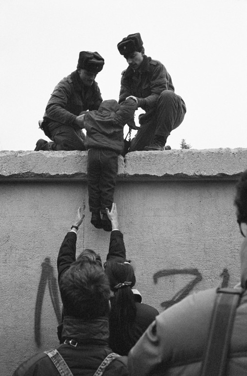 . East German border guards lift a child onto the Berlin Wall at the effective end of the city\'s partition, 31st December 1989. (Photo by Steve Eason/Hulton Archive/Getty Images)