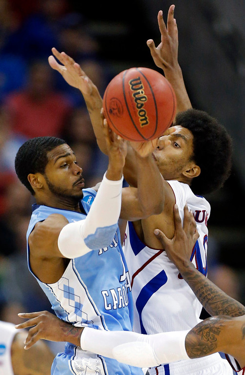 . North Carolina guard Dexter Strickland (1) passes to a teammate while covered by Kansas forward Kevin Young (40) during the first half of a third-round game in the NCAA college basketball tournament at the Sprint Center in Kansas City, Mo., Sunday, March 24, 2013. (AP Photo/Orlin Wagner)
