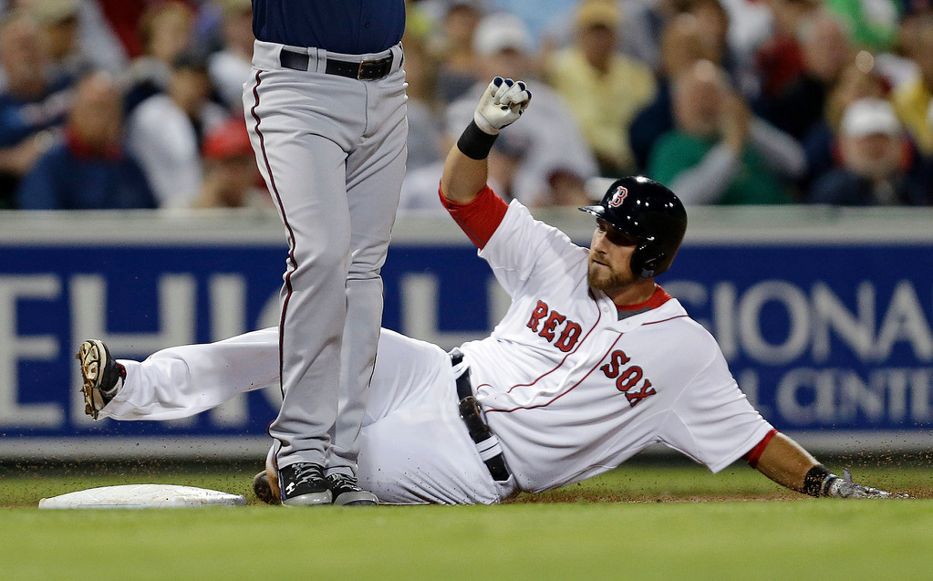 . Boston Red Sox Will Middlebrooks slides into third on a triple as Minnesota Twins third baseman Trevor Plouffe covers the bag in the fifth inning. (AP Photo/Gerald Herbert)