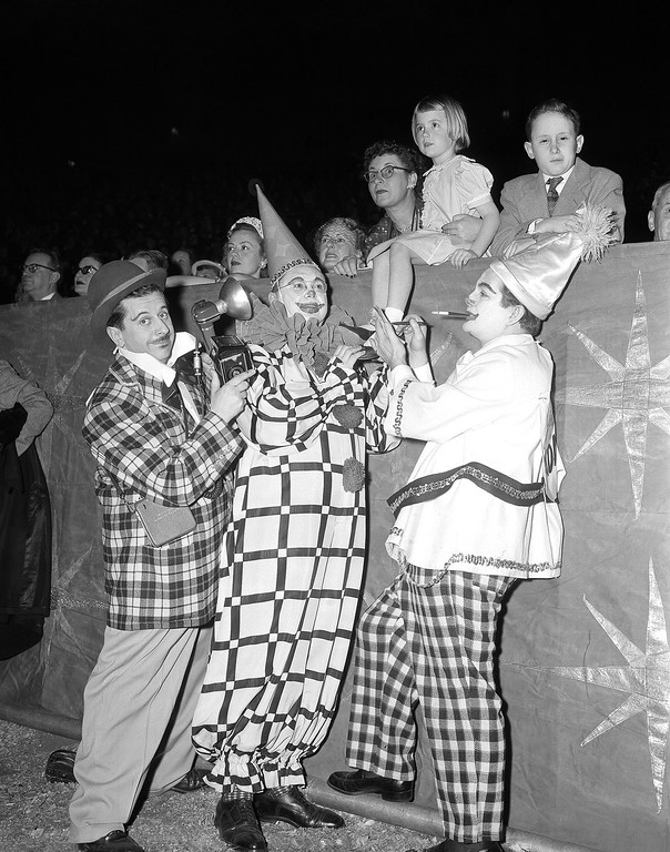 . Stars of entertainment field dressed as clowns are, left to right, Morey Amsterdam, Sam Levinson and Joey Adams, performing at gala opening night benefit for United Cerebral Palsy of New York, of the Ringling Bros. and Barnum and Bailey Circus at Madison Square Garden, New York, March 31, 1954. Their audience, above them, are from left: Magdalena Hayden, of New Orleans, La.; Sharon Erickson, seven, of Baltimore, and Bennett Shapiro, ten, of New York City. (AP Photo/Matty Zimmerman)