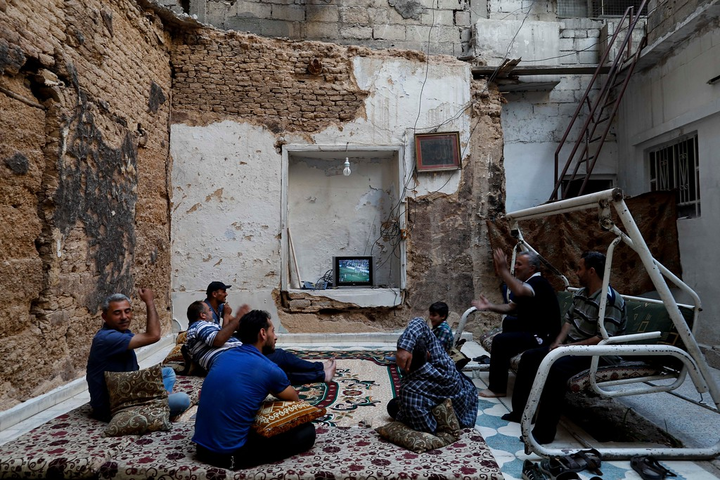 . Syrians react as France\'s Antoine Griezmann scores his side\'s second goal while watching the World Cup soccer final match between France and Croatia at their home that was partially destroyed by the war leaving two of its rooms without a ceiling in the town of Ain Terma, in the Eastern Ghouta suburb of Damascus, Syria, Sunday, July 15, 2018. (AP Photo/Hassan Ammar)