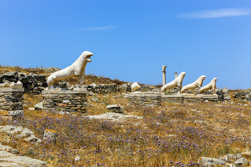 Four lion statues in the dry landscape of Delos.
