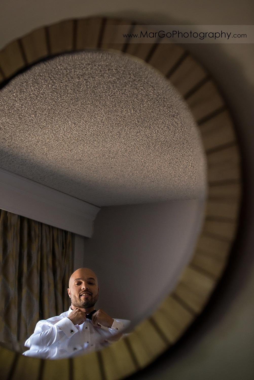 mirror shot of groom getting ready at Pleasanton Marriott