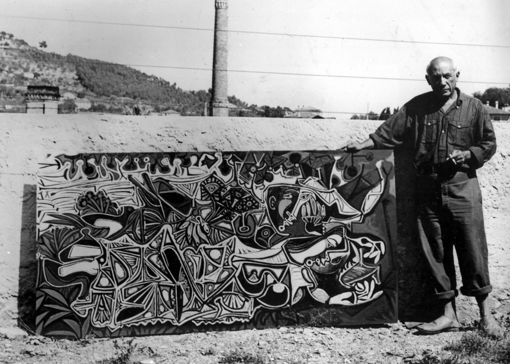 . Spanish born artist Pablo Picasso poses with one of his latest paintings in the garden of his studio at Vallauris on the French Riviera in Oct. 1950.   (AP Photo)