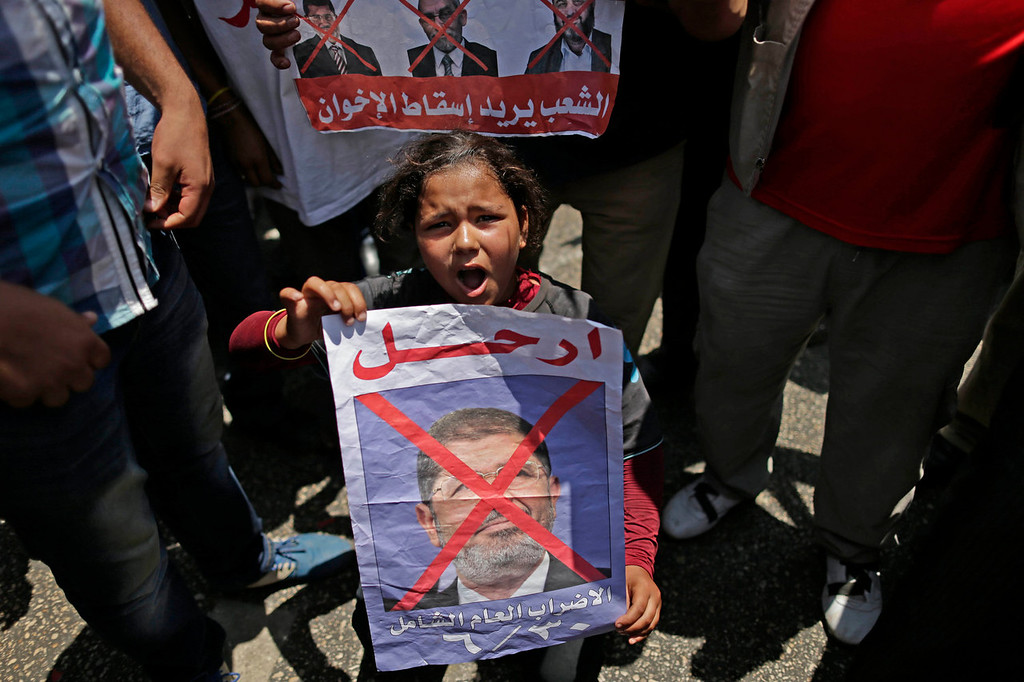 ". An Egyptian girl holds a poster with Arabic that reads, ""Heave, Huge year strike,\"" as she chants slogans during a protest against Egypt\'s Islamist President Mohammed Morsi outside the presidential palace, in Cairo, Egypt, Sunday, June 30, 2013. Organizers of a mass protest against Morsi claimed Saturday that more than 22 million people have signed their petition demanding the Islamist leader step down, asserting that the tally was a reflection of how much the public has turned against his rule.  (AP Photo/Hassan Ammar)"