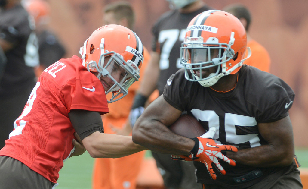 . Maribeth Joeright/MJoeright@News-Herald.com <p> Browns quarterback Johnny Manziel hands off to Chris Ogbonnaya  during mini camp in Berea, June 10, 2014.