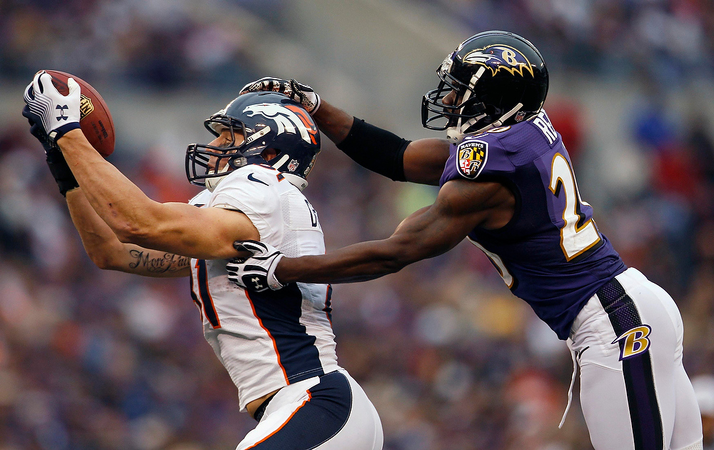 . Denver Broncos tight end Joel Dreessen (L) catches a pass deep in Baltimore Raven territory against Ravens safety Ed Reed (R) during the second half of their NFL football game in Baltimore December 16, 2012. The catch set up a Broncos\' touchdown on the next play.  REUTERS/Gary Cameron
