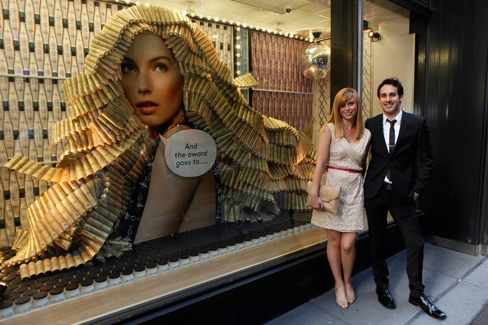 . Nexxus contest winner, Julie Christianson and guest Mark Oxman pose in front of the Nexxus window display prior to 2013 Tony Awards on June 9, 2013 in New York City.  (Photo by Thos Robinson/Getty Images for Nexxus)