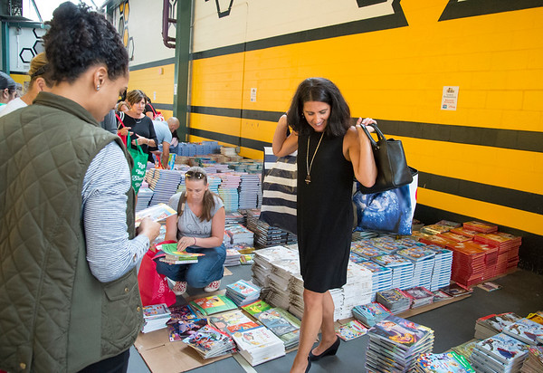 09/04/19 Wesley Bunnell | StaffrrTwenty two thousand books were donated to area educators and parents with children by ESPN and Disney on Thursday September 4, 2019 at New Britain Stadium. Jennifer Shannon from Reggio Magnet School of the Arts carries two bags of books as she prepares to leave.