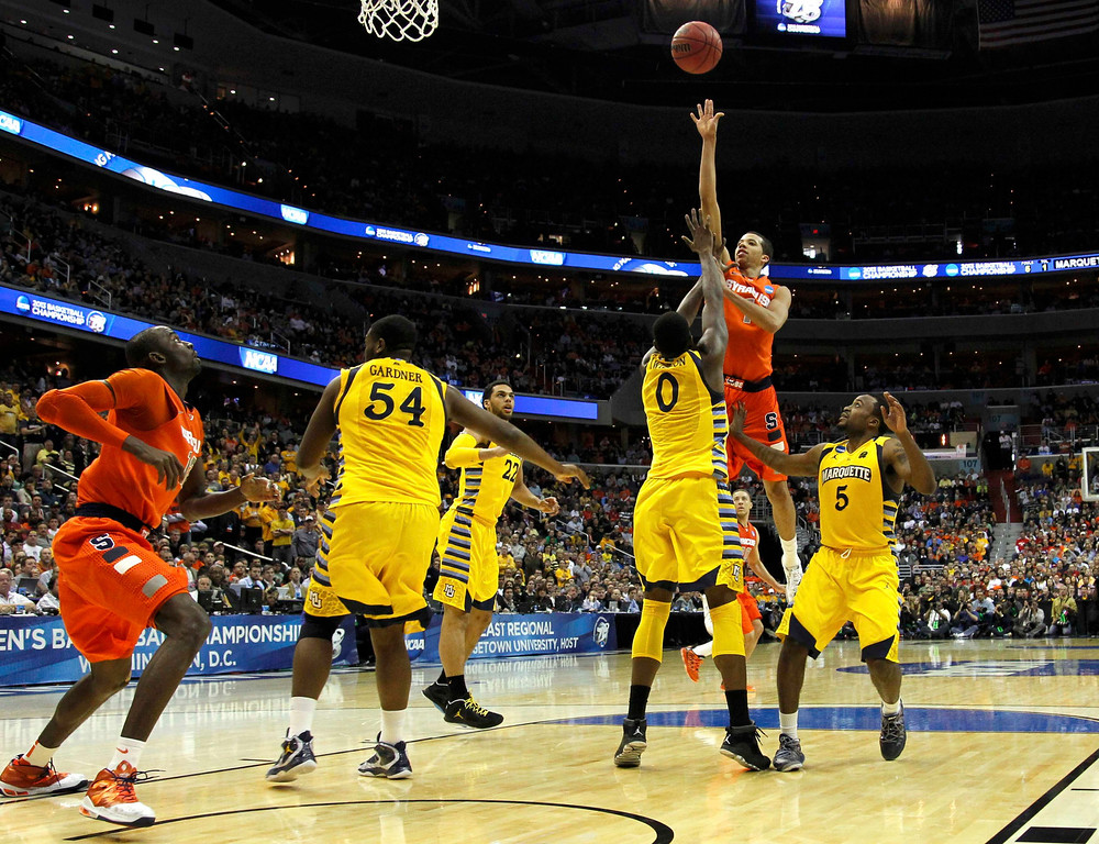 . Syracuse Orange guard Michael Carter-Williams shoots over Marquette Golden Eagles forward Jamil Wilson during the second half in their East Regional NCAA men\'s basketball game in Washington, March 30, 2013. REUTERS/Jason Reed