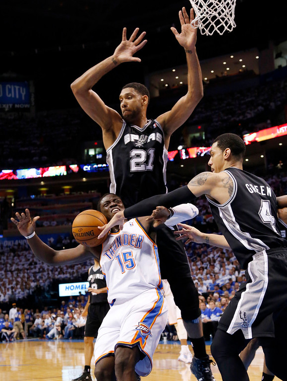 . San Antonio Spurs guard Danny Green (4) knocks the ball away from Oklahoma City Thunder guard Reggie Jackson (15) in front of Spurs forward Tim Duncan (21) in the first quarter of Game 4 of the Western Conference finals NBA basketball playoff series in Oklahoma City, Tuesday, May 27, 2014.  (AP Photo/Sue Ogrocki)