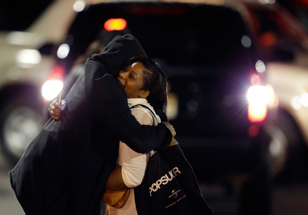 . A woman, right, is reunited with a man in the parking lot of Garden State Plaza Mall following reports of a shooter, Tuesday, Nov. 5, 2013, in Paramus, N.J. Hundreds of law enforcement officers converged on the mall Monday night after witnesses said multiple shots were fired there. (AP Photo/Julio Cortez)