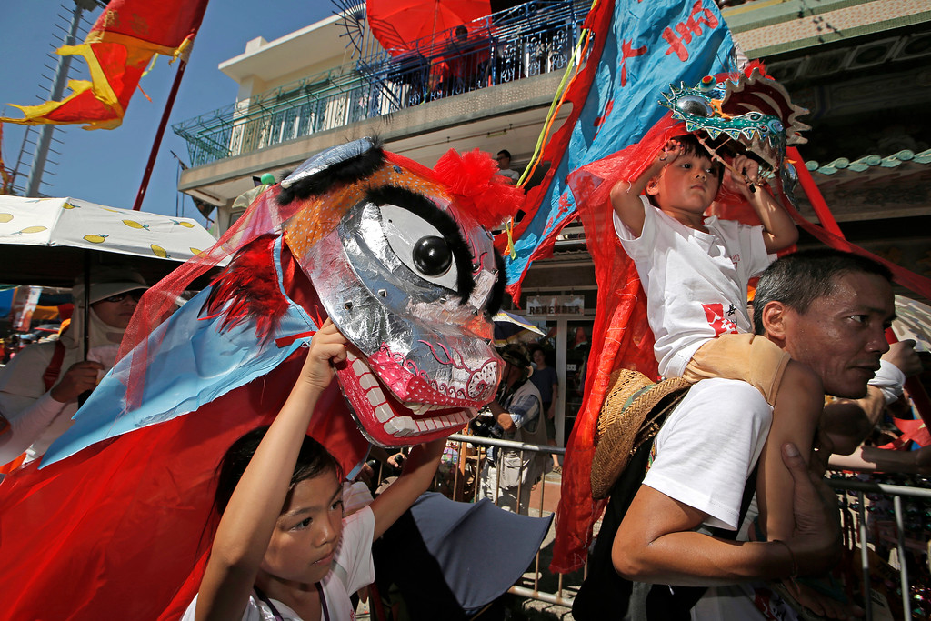 . A children perform lion dance during a parade on the outlying Cheung Chau island in Hong Kong to celebrate the Bun Festival Tuesday, May 22, 2018. Thousands of local residents and tourists flocked to an outlying island in Hong Kong to celebrate a local bun festival on Tuesday despite the recording-breaking heat.  The festival features a parade with children dressed as deities floated on poles. Later on Tuesday, contestants will take part in bun-scrambling competition. They will race up a 14-meter bamboo tower to snatch as many plastics buns as possible. Buns that are higher up are worth more points.  (AP Photo/Kin Cheung)