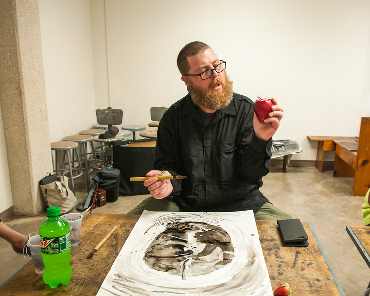 Rob Neal drawing an apple for his Drawing II class in the Center for the Arts.