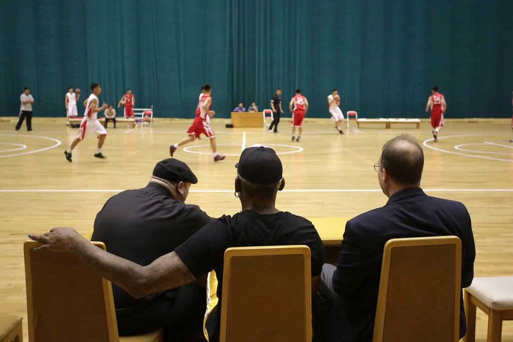 . Former NBA basketball star Dennis Rodman, center, with Joseph Terwilliger, academic at Columbia University, and colleague Chris Volo, left, watches North Korean basketball players in a game Thursday, June 15, 2017, in Pyongyang, North Korea. (AP Photo/Kim Kwang Hyon)