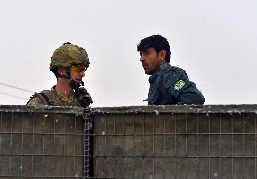 Description of . An Afghan policeman (R) talks to a NATO soldier (L) at the site of an explosion in Kabul on December 17, 2012. A car bomb exploded at a compound owned by a US-based construction company under contract to the Afghan army, killing at least one person and wounding 15, police said. Five foreigners including those from the US and South Africa were among the wounded, a security source at the company told AFP. MASSOUD HOSSAINI/AFP/Getty Images