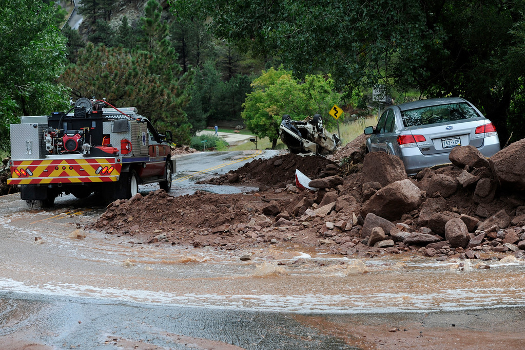 . BOULDER, CO - SEPTEMBER 13: A Brighton Fire and Rescue Truck drives down Linden at S. Cedar Brook Rd.  past a vehicle stuck in the mud and rocks at the intersection of Linden and S. Cedar Brook Rd. in Boulder Colorado Friday afternoon, September 13, 2013. The car, on the right, was swept off the road Wednesday evening in a mudslide due to flooding, it had four people inside, all got out, but two people were swept away and killed in the flooding, the other two were accounted for. (Photo By Andy Cross/The Denver Post)