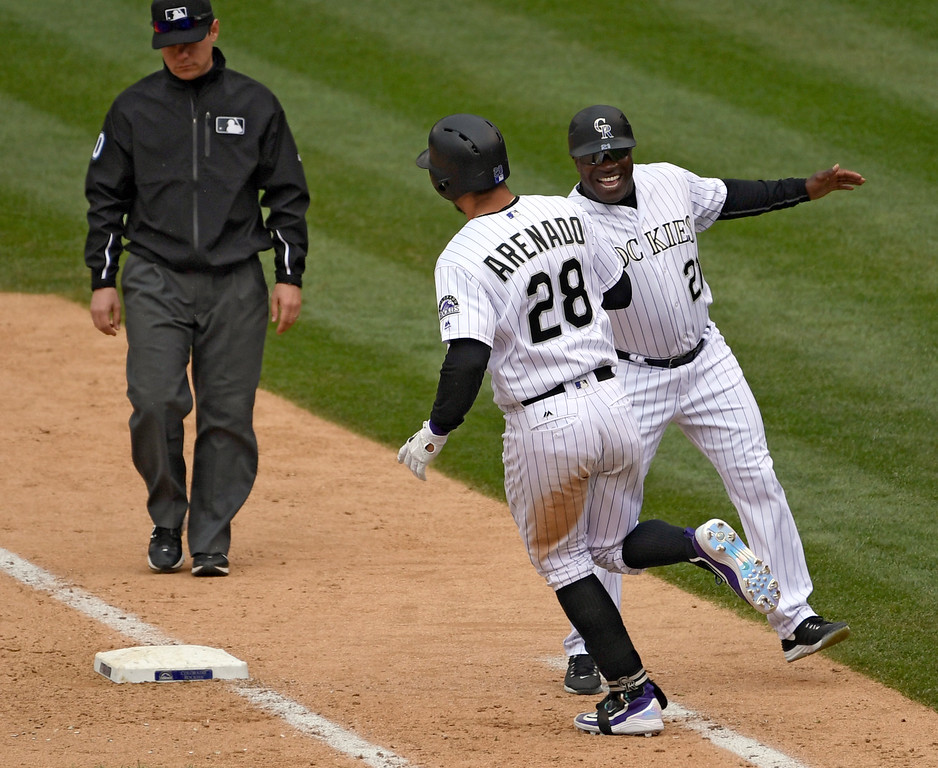 . DENVER, CO - MAY 11: Colorado Rockies third baseman Nolan Arenado (28) high fives first base coach Eric Young after hitting a home run in the 8th inning to put them up 8-7 over the Arizona Diamondbacks May 11, 2016 at Coors Field. The game would end with the Rockies over the Diamondbacks. (Photo By John Leyba/The Denver Post)