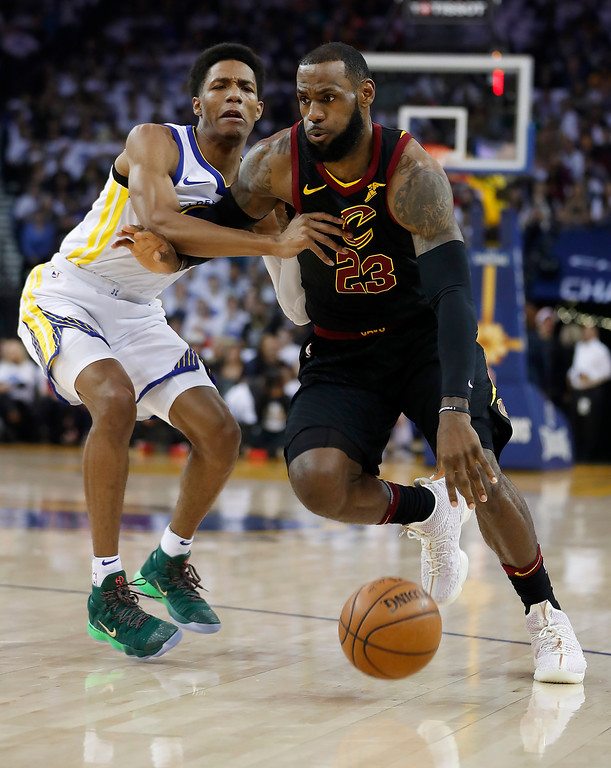 . Cleveland Cavaliers forward LeBron James (23) drives to the basket past Golden State Warriors guard Patrick McCaw during the first half of an NBA basketball game in Oakland, Calif., Monday, Dec. 25, 2017. (AP Photo/Tony Avelar)