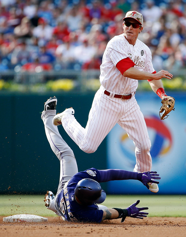 . Philadelphia Phillies second baseman Chase Utley, right, leaps over Colorado Rockies\' Carlos Gonzalez after forcing him out at second on a double play hit by Wilin Rosario during the second inning of a baseball game, Monday, May 26, 2014, in Philadelphia. Wilin was out at first on the play. (AP Photo/Matt Slocum)
