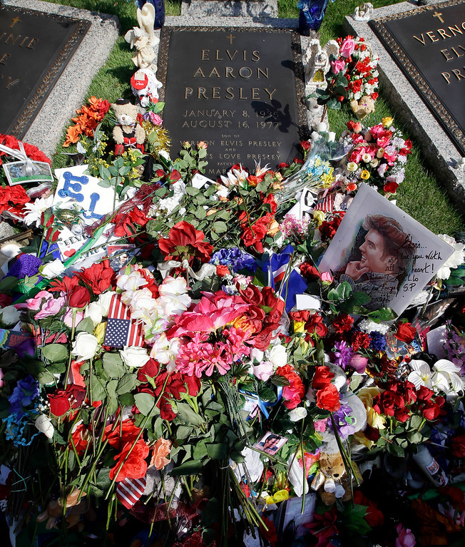 . FILE- This Aug. 16, 2012 file photo shows flowers left by fans on the grave of Elvis Presley at Graceland, Presley\'s Memphis, Tenn. home. Friends and fans of late singer and actor Elvis Presley are descending on Memphis, Tennessee, for Elvis Week, the annual celebration of his life and career. It coincides with the 40th anniversary of the passing of Presley, who died on Aug. 16, 1977. (AP Photo/Mark Humphrey, File)