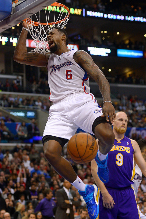 . The Clippers\' DeAndre Jordan dunks as the Lakers Chris Kaman looks on in the first half, Friday, January 10, 2014, at Staples Center. (Photo by Michael Owen Baker/L.A. Daily News)